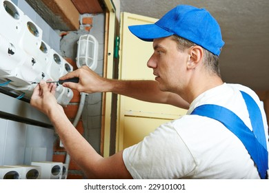 electrician engineer worker assembling fuseboard equipment meter in room