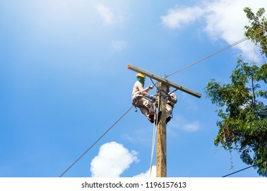 An electrician or engineer works on a power post and a high voltage system for maintenance. High-power distribution system is damaged.