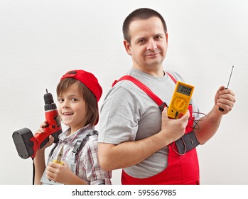 Electrician father and helping son ready for work - posing with tools in front of white wall