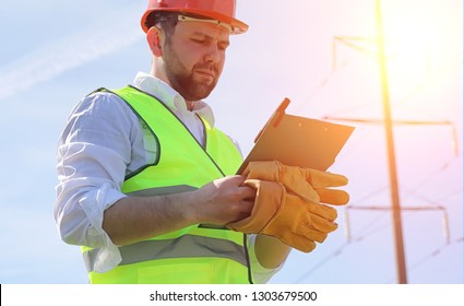 An electrician in the fields near the power transmission line. The electrician manages the process of erecting power lines. The mechanic in a helmet and a reflective form and special gloves at work.