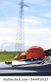 An electrician in the fields near the power transmission line. The electrician manages the process of erecting power lines. The mechanic in a helmet and a reflective form special gloves work.
