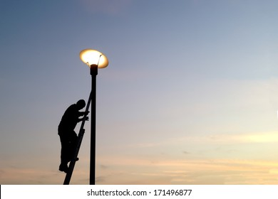 electrician fixing street light bulbs and climbing on a ladder