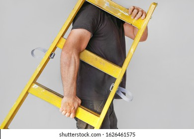 Electrician hand holds a yellow wooden ladder. Factory african worker with a yellow wooden staircase.The builder bears a wooden step-ladder on a gray background.