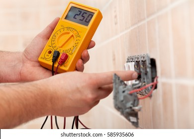 Electrician hands checking voltage in a partially mounted electrical socket - measuring with multimeter
