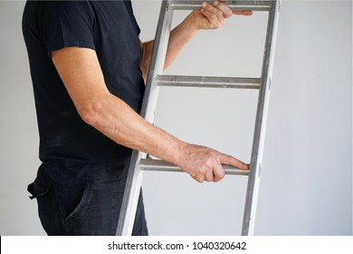 An electrician holds an aluminum ladder. The builder carries an aluminum stepladder. Worker of the plant with aluminum rung ladder