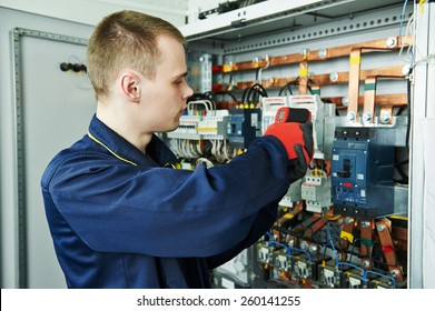 electrician inspector cheching power of fuseboard equipment in boiler room