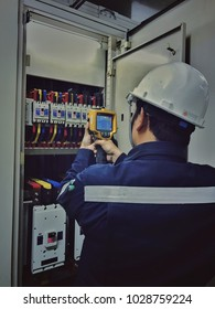 Electrician inspects the power control to find the abnormal condition of transformer by using thermo scanner.