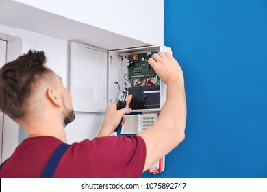 Electrician installing alarm system