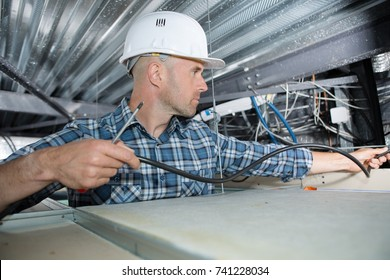 Electrician installing cable in roof space