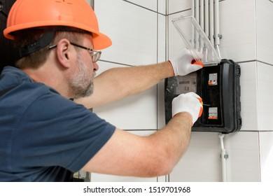 Der Elektriker installiert ein elektrisches Zähler an der Wand.