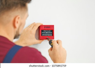 Electrician installing fire alarm system