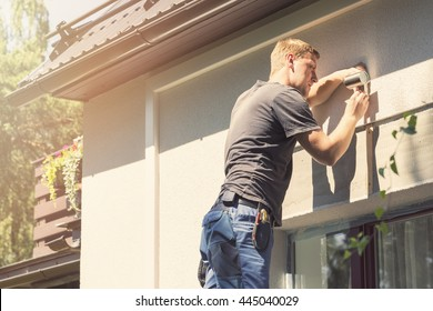 electrician installing lamp on house facade