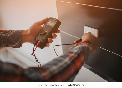 Electrician, Electrician installing new current socket with screwdriver. Installing electrical outlet or socket - closeup on electrician hands