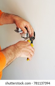 An electrician installing new electrical switches using pliers during the renovation of the house