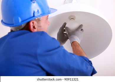 Electrician installing new light bulb