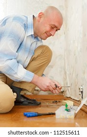 Electrician Installing Wall Socket in the house