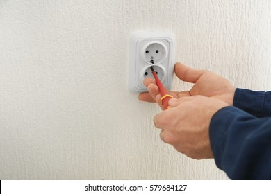 Electrician installing wall socket in new building, closeup