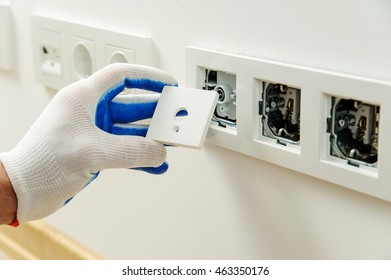 Electrician installs decorative frame on electric and TV sockets.
