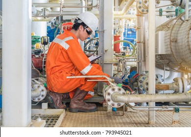 Electrician and Instrument technician working at offshore oil and gas central facility, He is checking level transmitter of inlet knock out drum of gas booster compressor before startup.