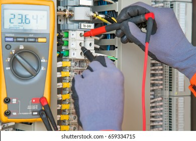 Electrician and instrument worker wearing safety gloves measuring voltage and checking electric circuit by using digital multi meter, maintenance and service job.