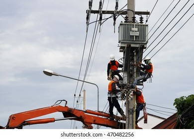 Electrician lineman repairman worker at climbing work on electric post power pole and change transformer