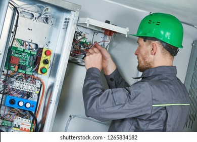 Electrician make maintenance in engine room of elevator