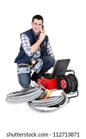 Electrician making a call whilst kneeling by his equipment