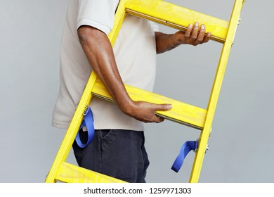 Electrician male holds a yellow wooden ladder. The builder bears a wooden step-ladder on a gray background. Factory worker with a yellow wooden staircase.