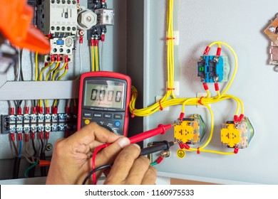 Electrician man testing electrical terminal box, control panel with magnetic contactor and overload relay,Measuring electrical  voltage at button switch on controlled box. Maintenance  concept.