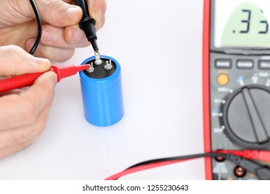 electrician is measuring a capacitor with testing tool