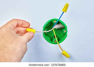 Electrician is mounting green round wall electrical box, electrical maintenance.