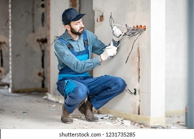 Electrician mounting wiring for electric sockets on the construction site of a new building indoors