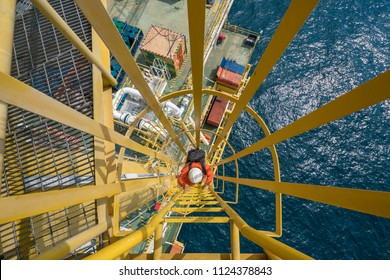 Electrician at offshore oil and gas processing platform carrying tool bag and stepping up to crane tower for service and repair electrical system.;