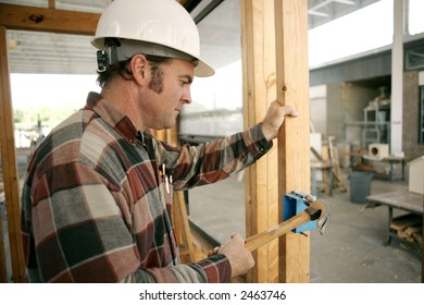 An electrician on a construction site hammering a switch box into a wood beam.  Model is a licensed master electrician. Work being performed to code.