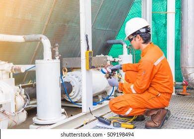 Electrician operator inspect and checking heating ventilated and air conditioning (HVAC), air conditioning service in offshore oil rig platform while worker charging refrigerant in system.