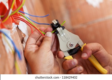 Electrician peeling off insulation from wires - closeup on hands and pliers