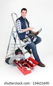 Electrician perched on step ladder