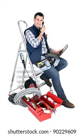 Electrician with a phone and laptop