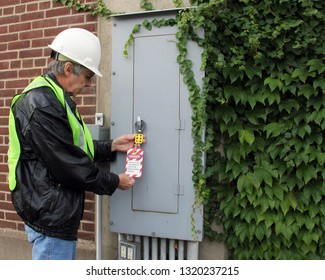 electrician places a safety lock out tag on a breaker panel