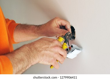 Electrician with pliers installing new electrical switches at the house renovation