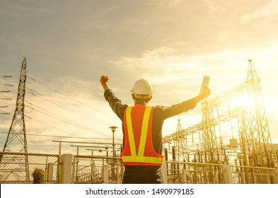 Electrician proudly raise their hands at the power substation against the sunrise background.