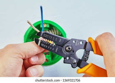 Electrician is removing insulation from wires of round electrical box with wire stripper cutter.