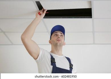 Electrician repairing ceiling light