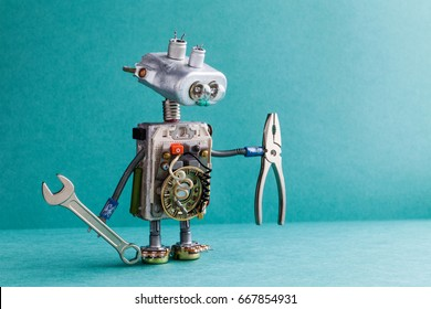 Electrician robot handyman wrench pliers. Mechanic cyborg toy lamp bulb eyes head, electric wires, capacitors vintage resistors. Green paper background copy text.