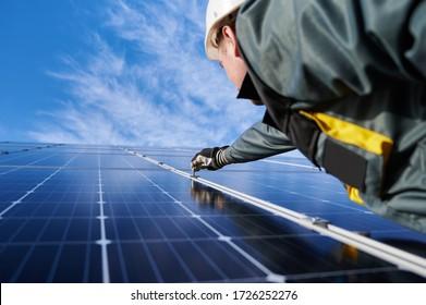 Elektrischer Schutzhelm, Uniform- und Arbeitshandschuhe, mit einer glänzenden neuen Solarbatterie mit Hexentaste, blauem Himmel im Hintergrund. Konzept alternativer grüner Energiequellen und Innovationen.