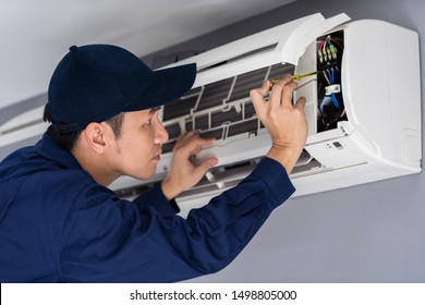 Electrician with screwdriver repairing the air conditioner indoors