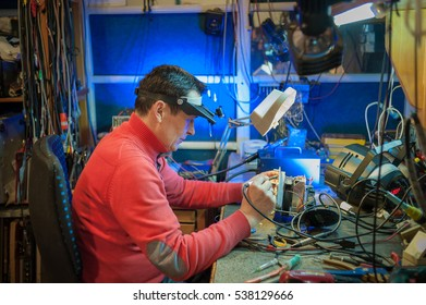 Electrician with soldering iron repairs device for stage lighting