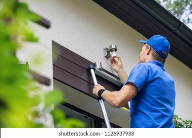 electrician standing on ladder and change the light bulb in house facade lamp