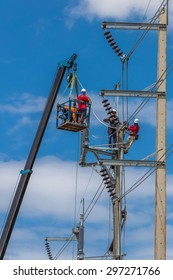 Electrician stays on the tower pole and repairs a wire of the power line