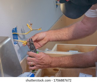Electrician stripping wire installing wall socket in new remodel house